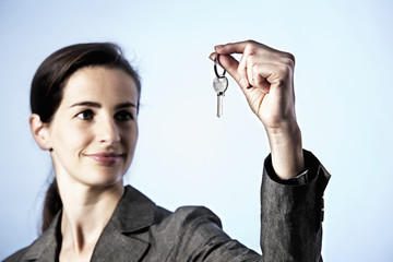 Business woman holding key between fingers