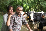 Farmer and his wife in front of their cows