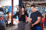 Mechanic Showing Tire to Woman Customer