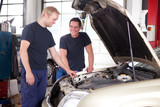 Two Mechanics Working on a Car