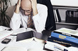 Businessman leaning over office desk studying