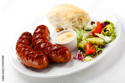 Grilled sausages, breadroll and vegetables