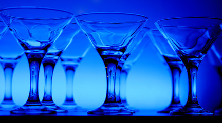Wineglasses arranged in rows on the table in blue light