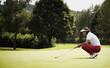 Golfer examining green before putting.