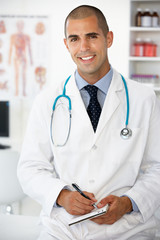 Young male doctor writing prescription