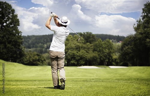 Man teeing-off golf ball.