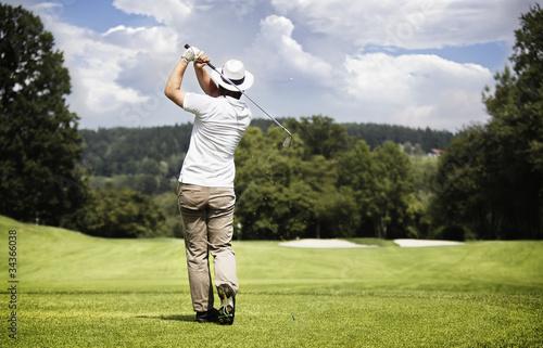 Man teeing-off golf ball.