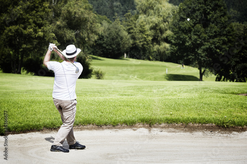 Golfer chipping in bunker.