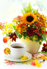 fall still life with cup of tea and autumnal flowers