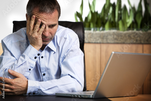 Frustrated businessman at laptop.