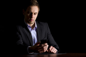 Business executive checking text messages on phone.