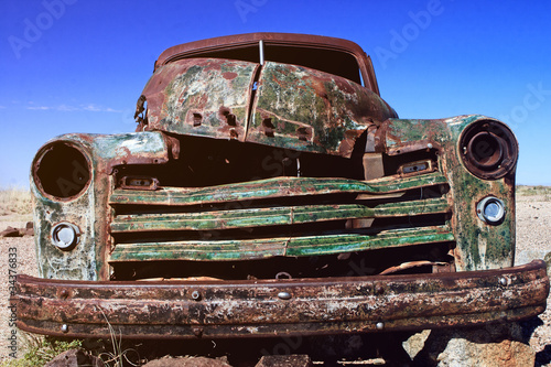 Front view of a rusted old vintage car, wrecked