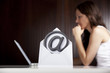 Emailing concept: At letter with woman and laptop.