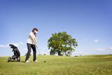 Woman focusing on golf fairway. poster