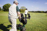 Gold couple walking on fairway with bags. poster