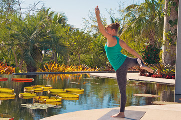 woman doing yoga outdoors in dancer variation pose side view