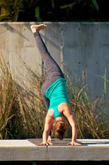 woman doing yoga outdoors in three leg down dog pose