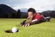 Golfer playing billiard on green.