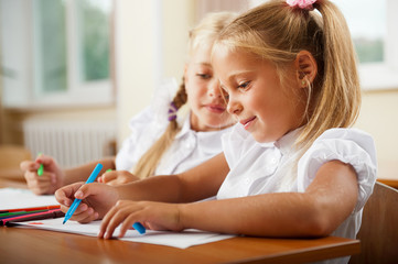 Little girls drawing pictures and writing letters to Santa Claus
