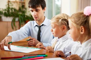 Teacher helping students with schoolwork in school classroom. Ho