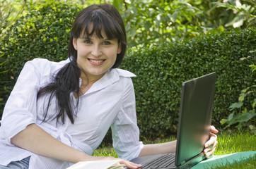 Junge Frau mit Büchern und Laptop im Garten