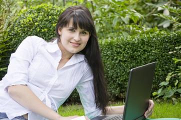 Junge Frau mit Laptop im Garten