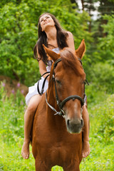 young smiling woman riding horse
