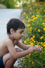 bambino che raccoglie un fiore in giardino