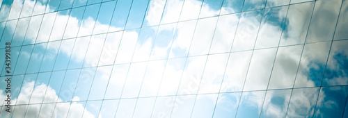 white clouds and azure sky reflected in mirror windows