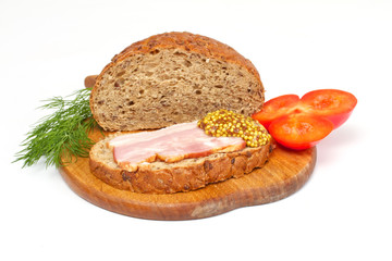 Bread with ham, mustard, dill and tomato on the wood plate