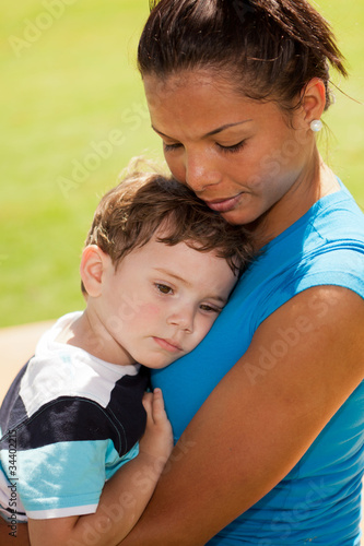 Pretty hispanic woman with baby boy in a park setting