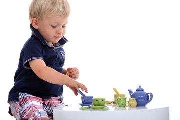 little boy playing with a doll's tea set