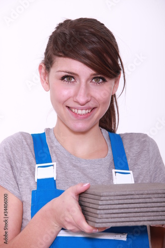 Woman holding pile of tiles
