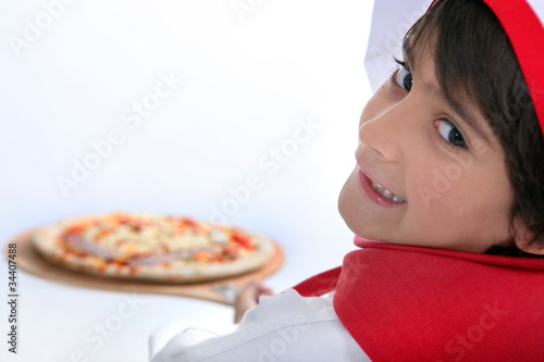 Young boy making pizza