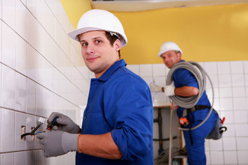 Men fitting electrical sockets