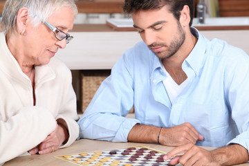 Senior woman and young man playing checkers