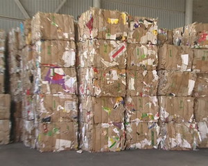 Huge heap of pressed paper placed in warehouse. Paper recycling.