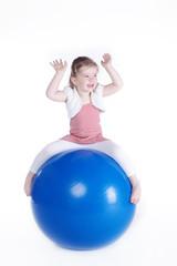 Kleines Mädchen sitzt auf Sport Ball und hat Spaß