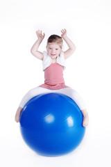 Kleines Mädchen sitzt auf Sport Ball und lacht