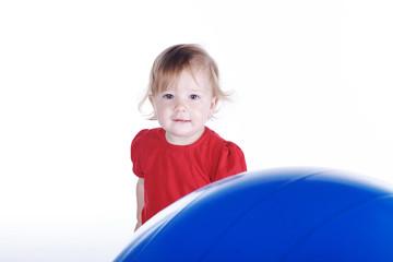 Kleines Mädchen blickt hinter großem Sport Ball hervor