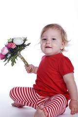 Kleines Mädchen mit Blumenstrauß sitzt