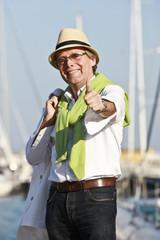Lachender Mann mit Daumen nach oben, am Yachthafen