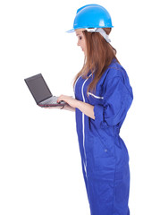 young woman worker in coveralls and helmet with laptop