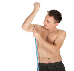 young shirtless man measuring himself arm