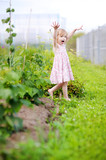 Adorable little girl fooling around in a garden poster