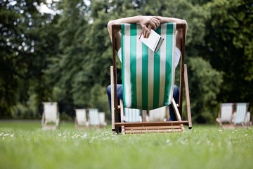 A young man relaxing on a deckchair, holding a guidebook