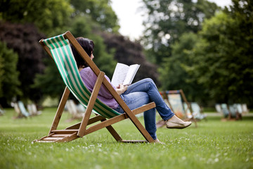 A young woman sitting on a deckchair, looking at a guidebook