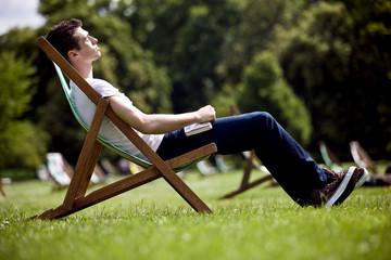A young man sitting on a deckchair, enjoying the sunshine