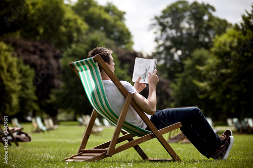 A young man sitting on a deckchair, looking at a guidebook