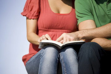 A young couple sitting, reading a guidebook